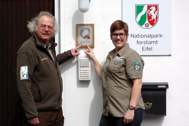 Nationalparkleiter Henning Walter und Qualitätscoach Martina Höller freuen sich über das neue Zertifizierungs-Schild am Eingang der Nationalparkverwaltung. Es signalisiert, dass sich das Nationalparkforstamt in besonderem Maße der Servicequalität verschrieben hat. (Foto: Nationalparkverwaltung Eifel)