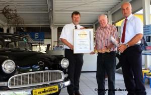 Vor einem Opel Rekord (Bj. 1956) übergeben Uwe Günther (Geschäftsführer Kreis Handwerkerschaft, l.) und der Stellvertretende Innungsmeister Reiner Wiluda (r.) den goldenen an Dieter Schiesberg.